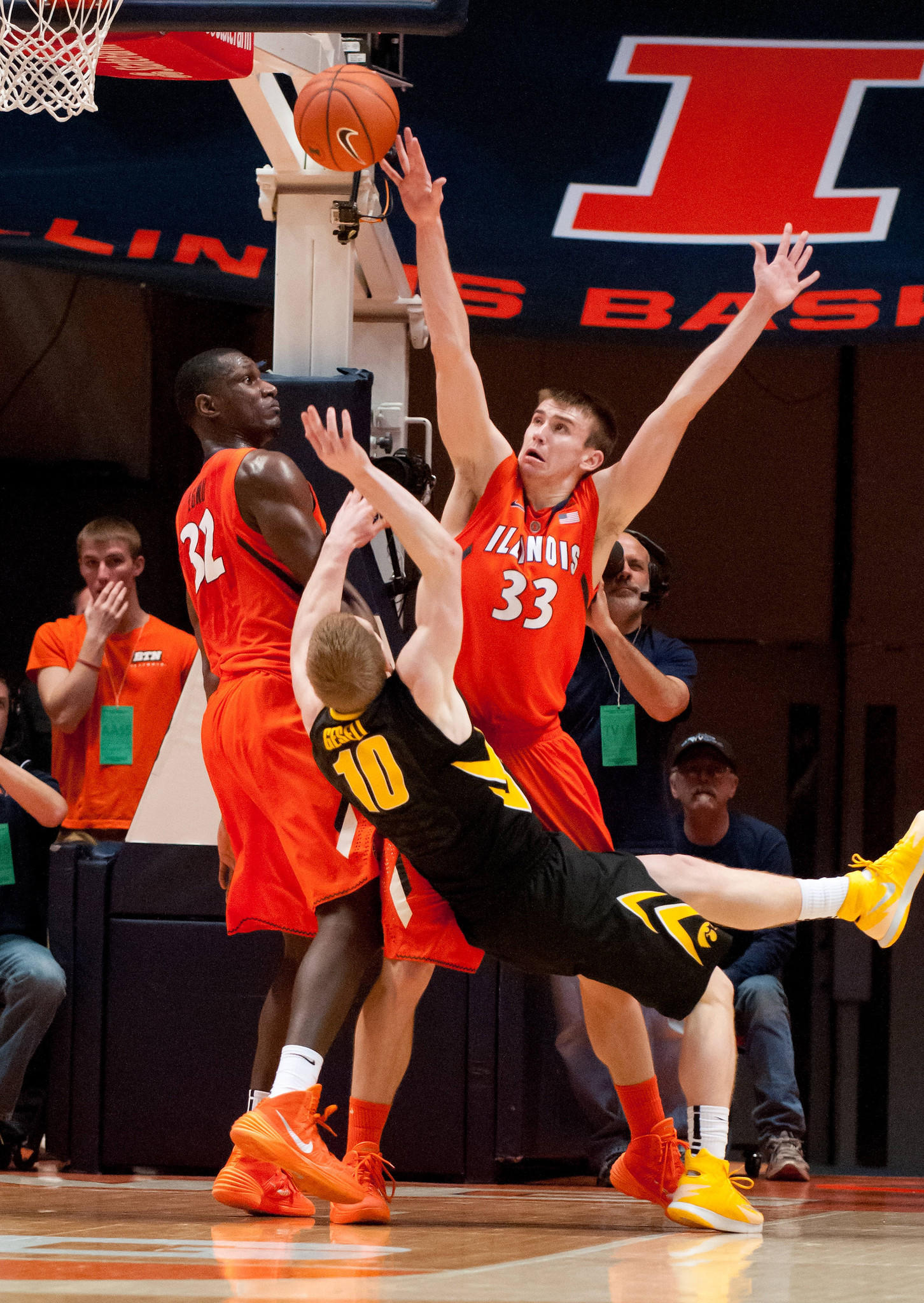 Iowa Hawkeyes guard Mike Gesell (10) shoots the ball while being defended by Illinois Fighting Illini forward/center Nnanna Egwu (32) and forward Jon Ekey (33) during the first half at State Farm Center.