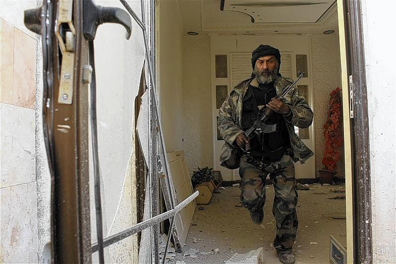 A Free Syrian Army fighter runs in a damaged building during clashes with forces loyal to Syria's President Bashar al-Assad in Old Aleppo