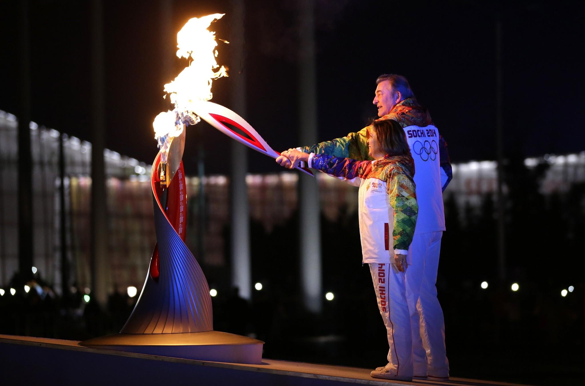 Russia's torchbearers Irina Rodnina (L) and Vladislav Tretyak light the Olympic cauldron at the opening ceremony of the 2014 Winter Olympics on February 7, 2014, in Sochi.