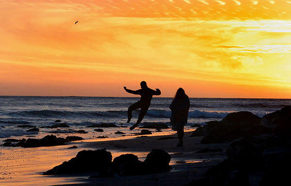 A man jumps on the beach as the sun sets over the Pacific Ocean in Sunset Beach in Pacific Palisades, Calif.