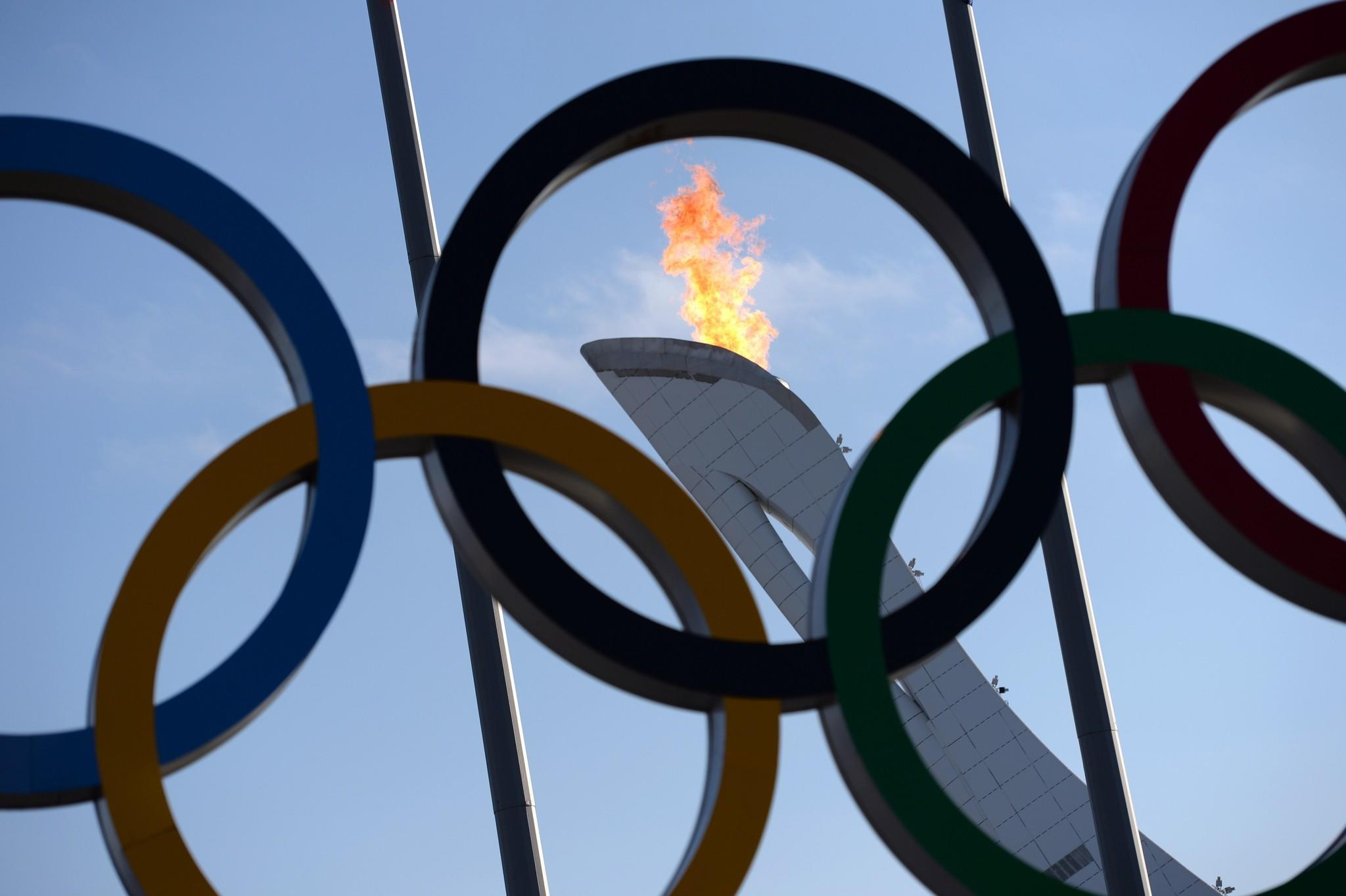 The Olympic flame is seen through the Olympic rings at Olympic Park.