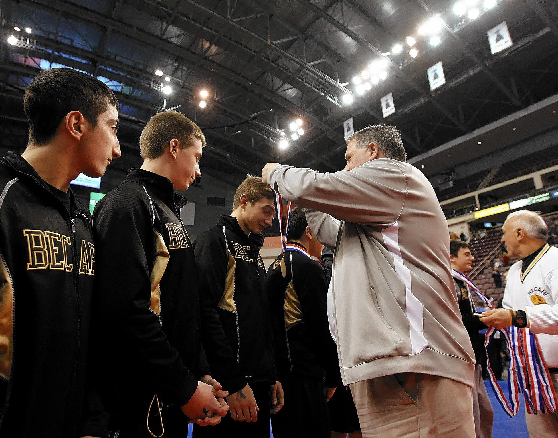 Bethlehem Catholic High School principal John Petruzzelli hands out gold medals to the team after the Golden Hawks beat Reynolds during the PIAA Class 2A Team Wrestling Championships on Saturday at the Giant Center in Hershey.