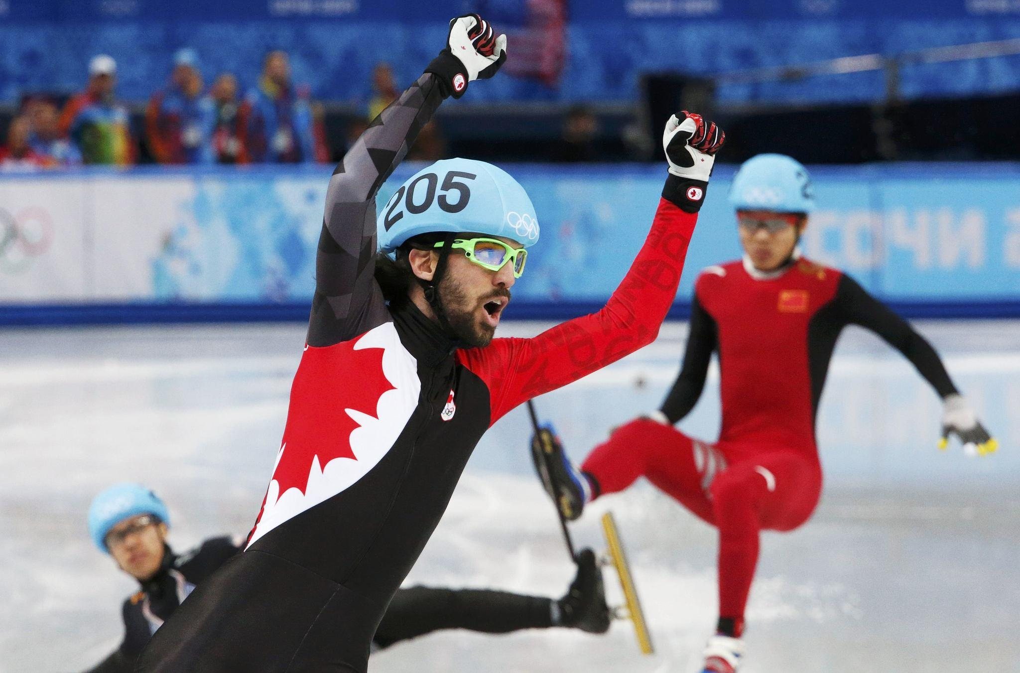 Canada's Charles Hamelin celebrates winning as China's Chen Dequan (back R) and J.R. Celski of the U.S. (bottom L) fall, during the men's 1,500.