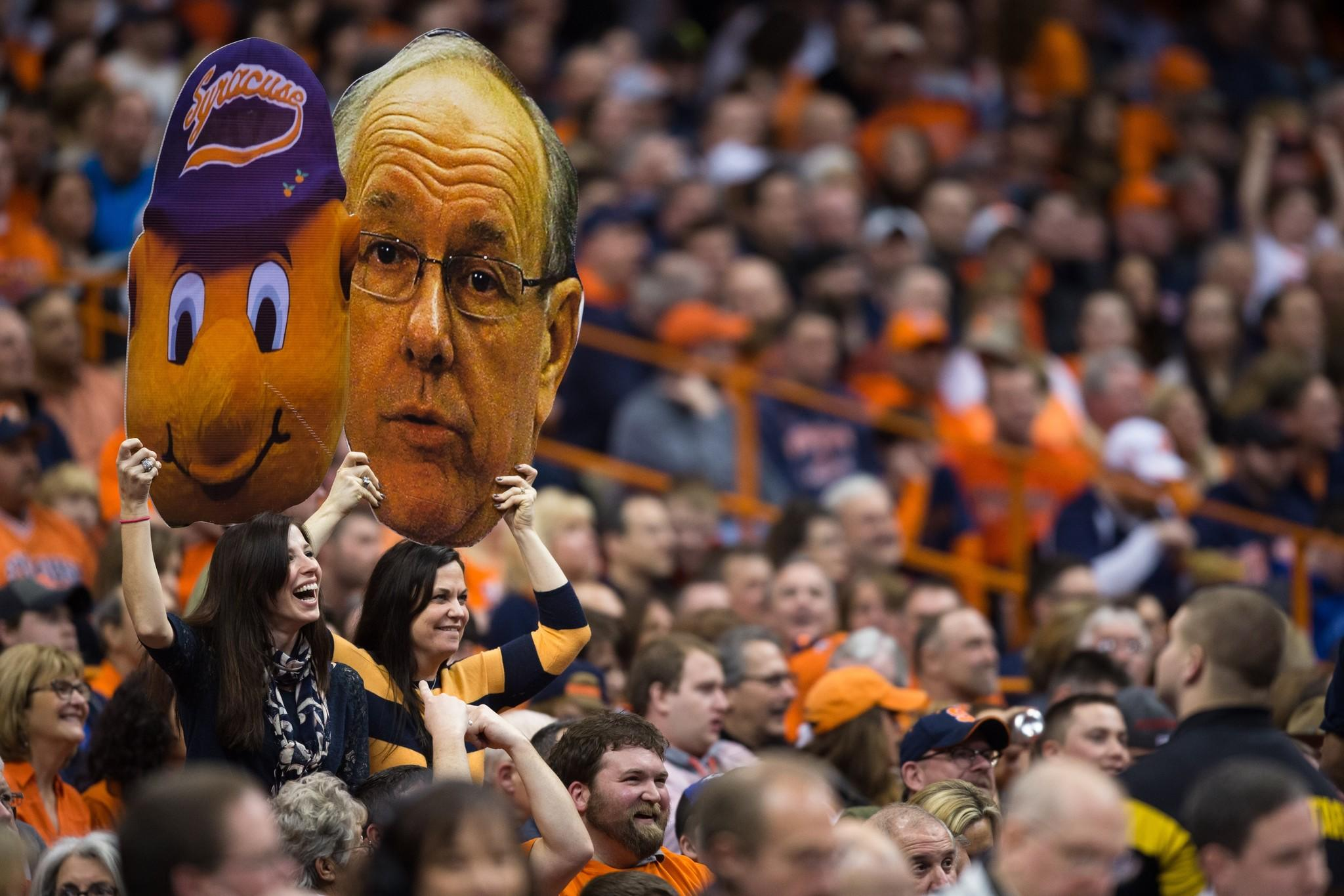 Syracuse fans hold up jumbo photographs of the team's mascot Otto and coach Jim Boeheim.