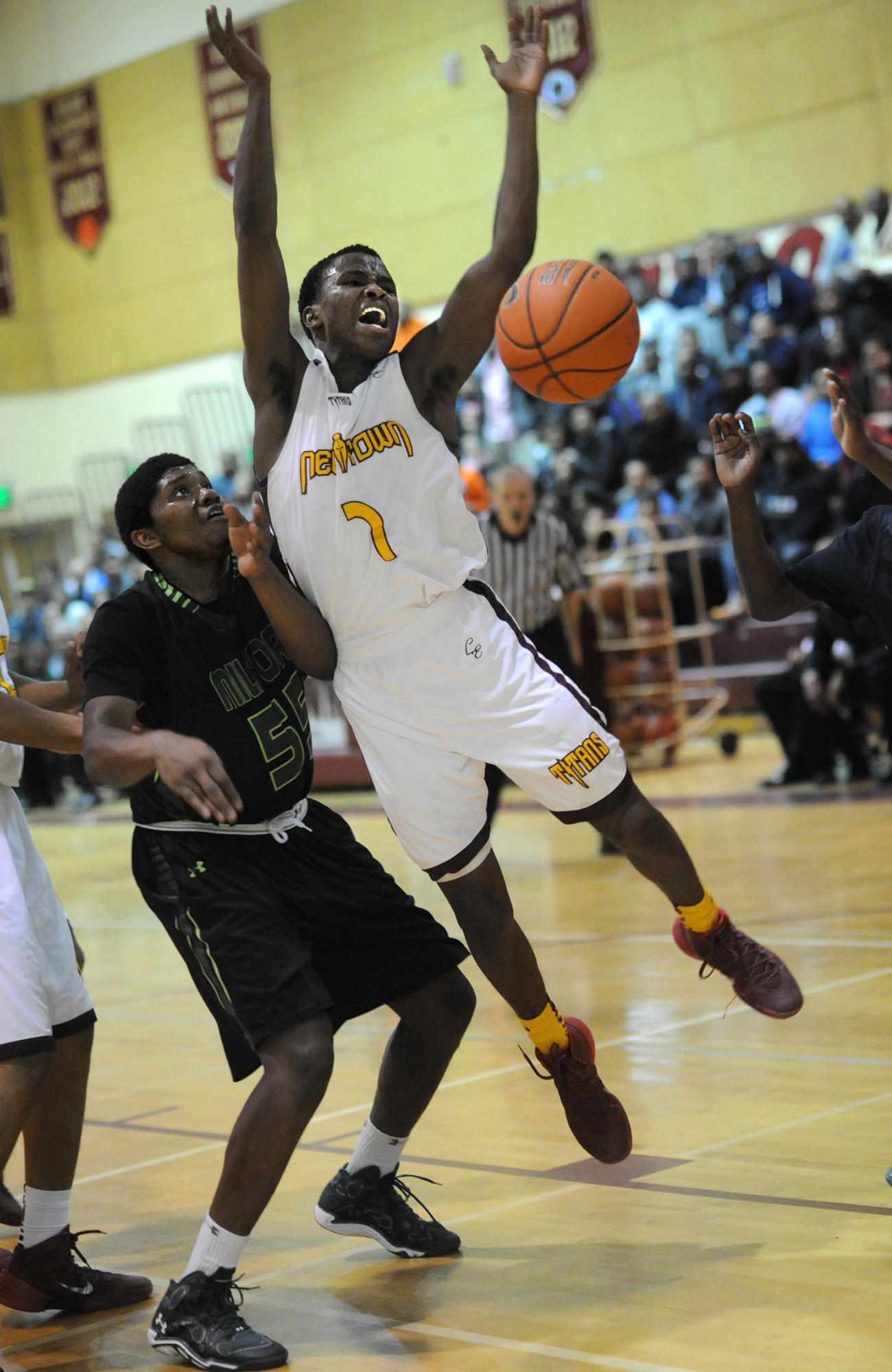 New Town's Danny Shand goes up for the ball against Milford Mill's Allen Costley in the fourth quarter.