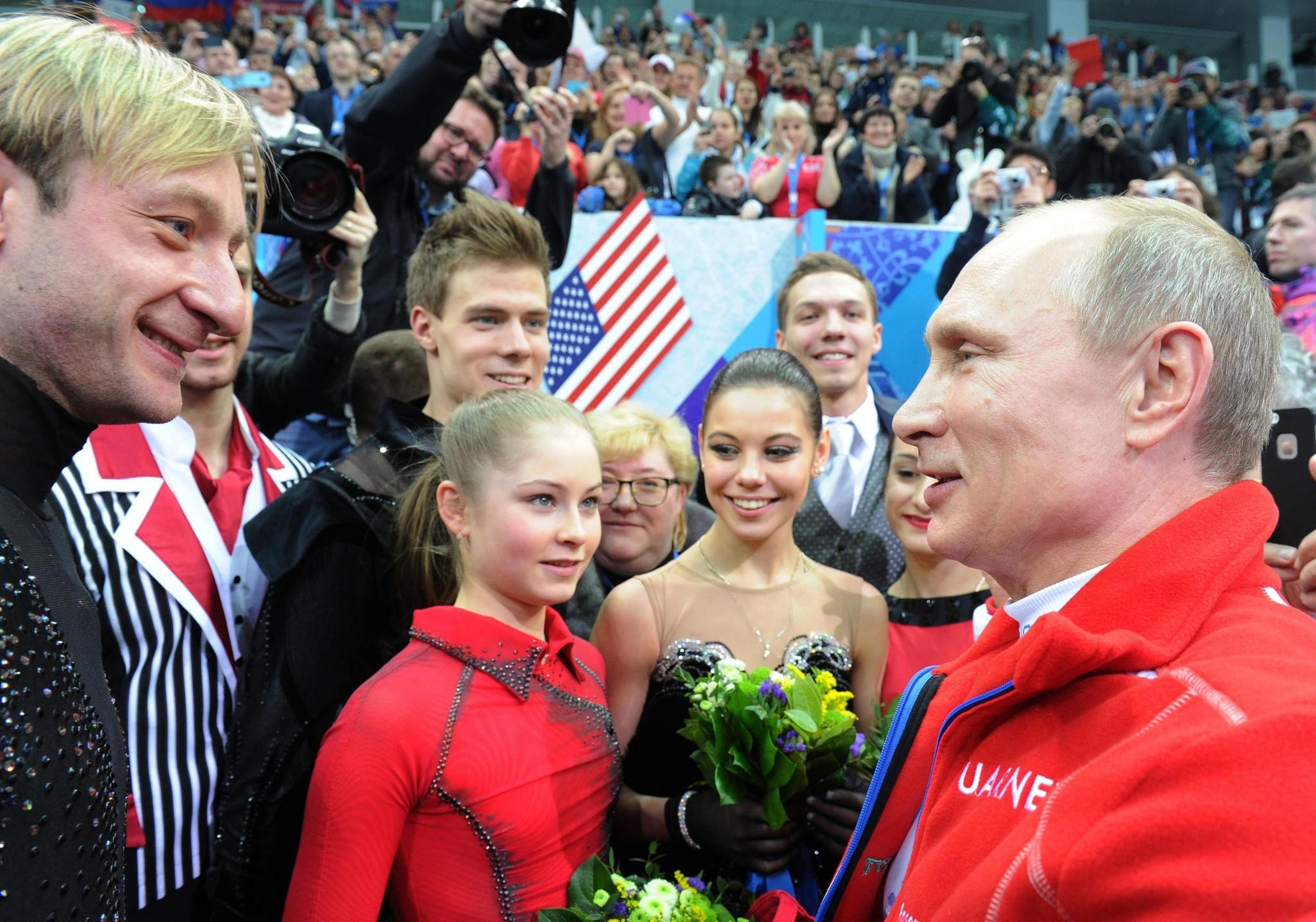Russia's President Vladimir Putin (right) speaks with Evgeny Plushenko (from left), Yulia Lipnitskaia and other Russian figure skaters after watching the Women's Figure Skating Team Free Program at the Iceberg Skating Palace.