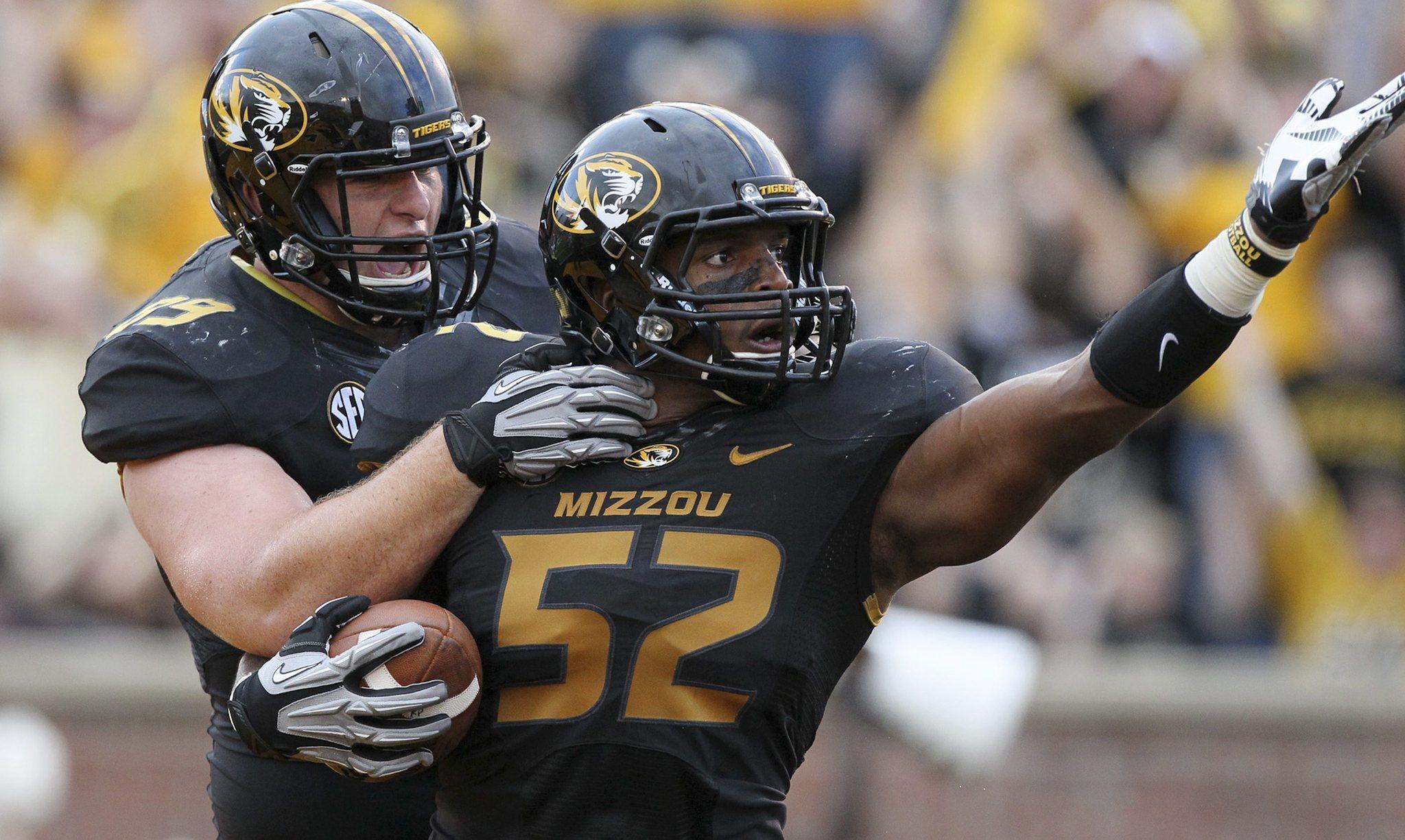 Missouri linebacker Michael Sam (52) is congratulated by teammate Matt Hoch after returning a fumble seven yards for a touchdown.