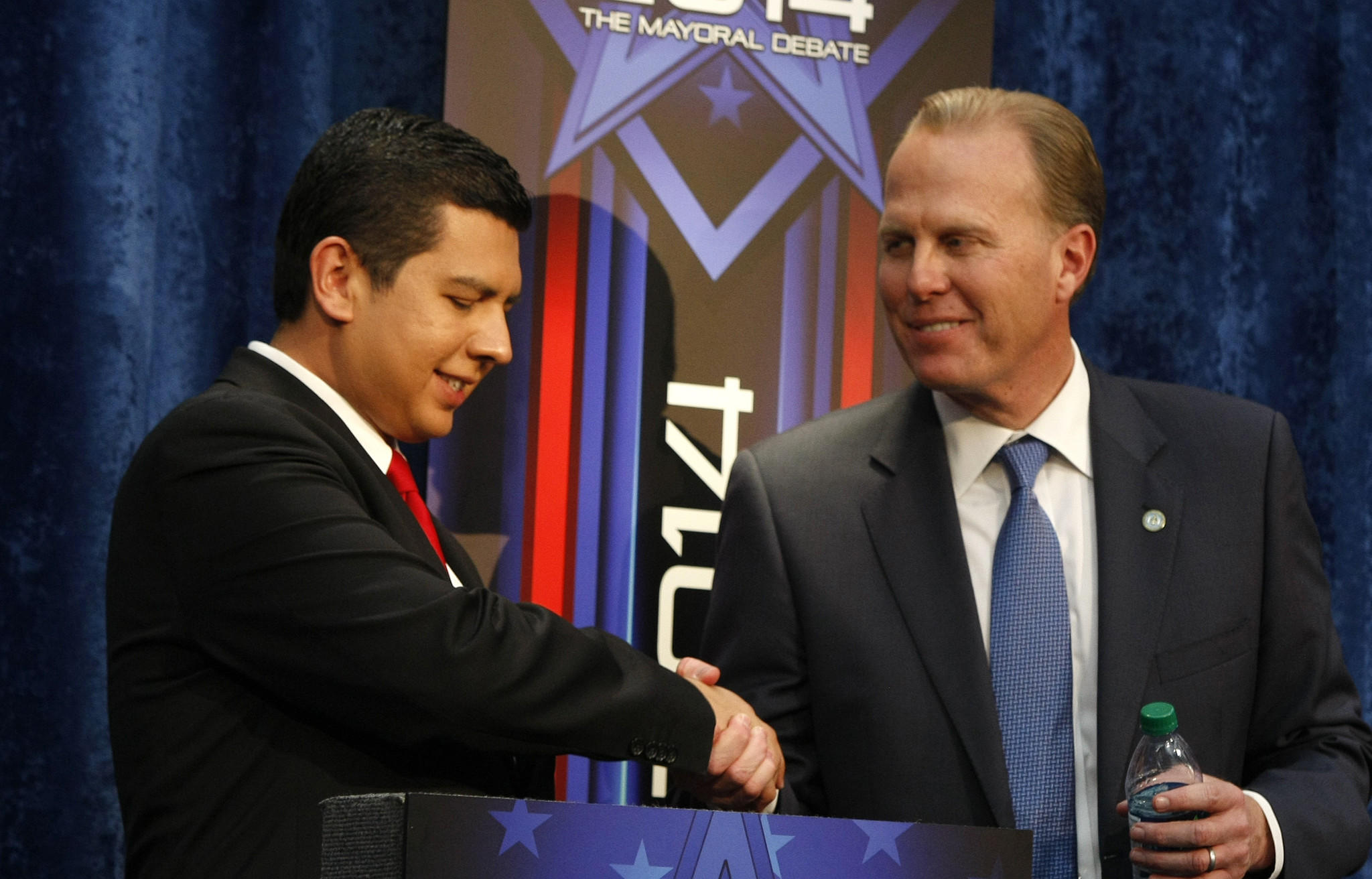 San Diego mayoral candidates David Alvarez, left, and Kevin Faulconer shake hands after a contentious debate. The runoff will decide a replacement for ex-mayor Bob Filner.