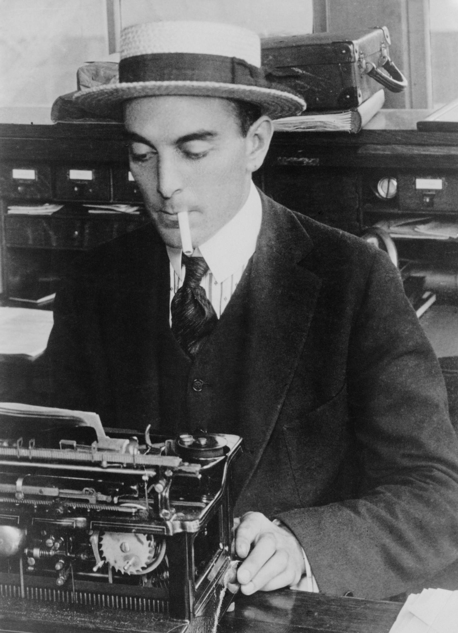 American sportswriter and humorist Ring Lardner (1885-1933) smokes a cigarette and types while sitting at a desk. He wears a straw boater.