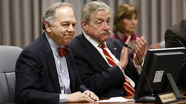 New Metra Chairman Martin J. Oberman is applauded by borad member John Plante.