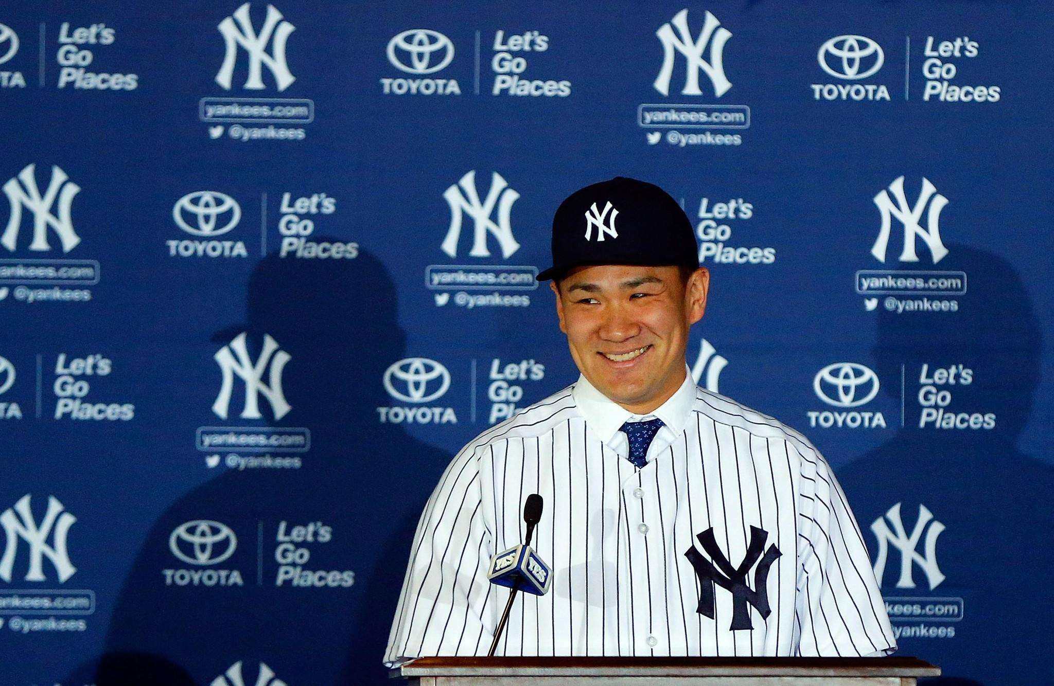 Masahiro Tanaka of the New York Yankees smiles as he is introduced to the media during a news conference.