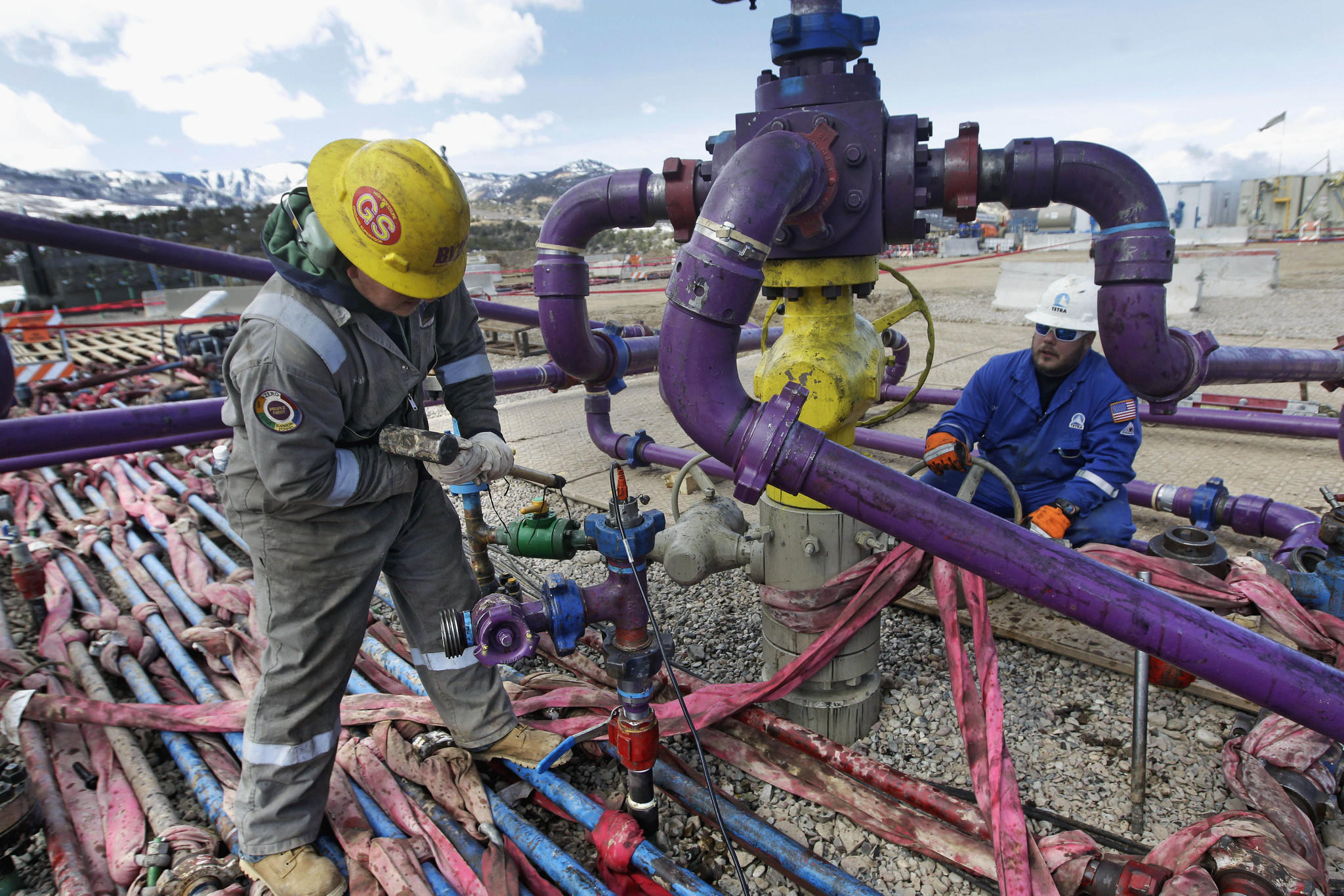 Workers tend to a wellhead at a hydraulic fracturing operation in western Colorado.