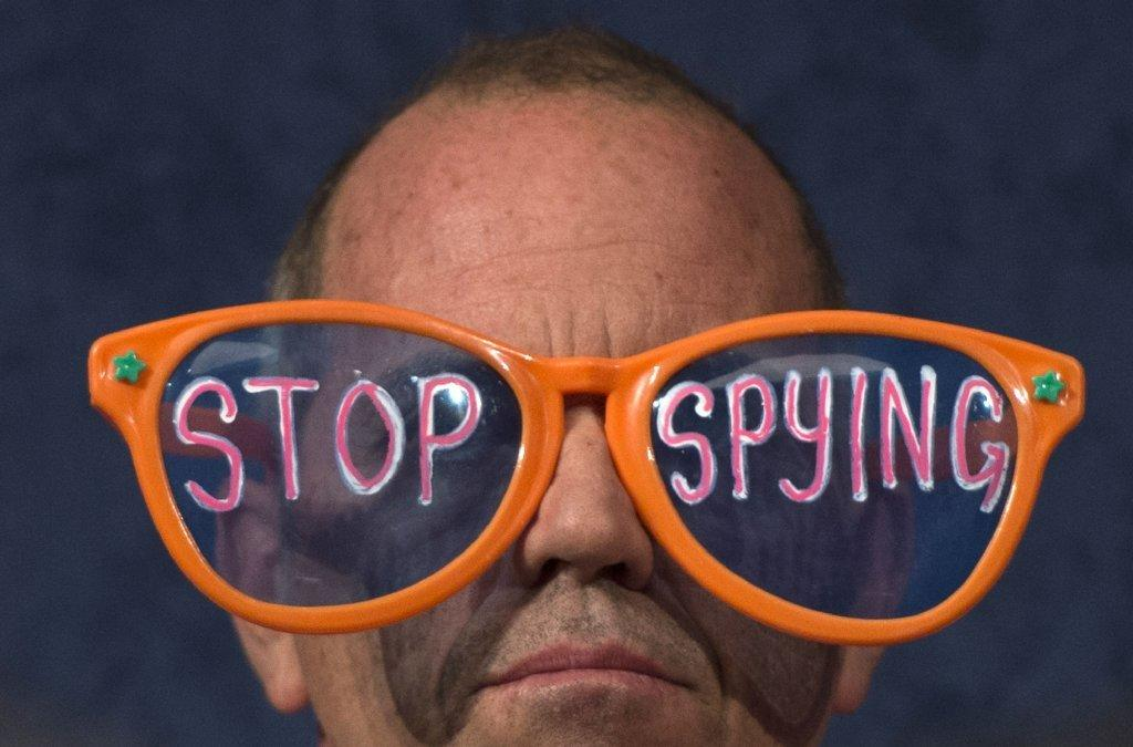 "A Code Pink protester wears giant glasses with the message ""Stop Spying"" at a congressional hearing in Washington, D.C."
