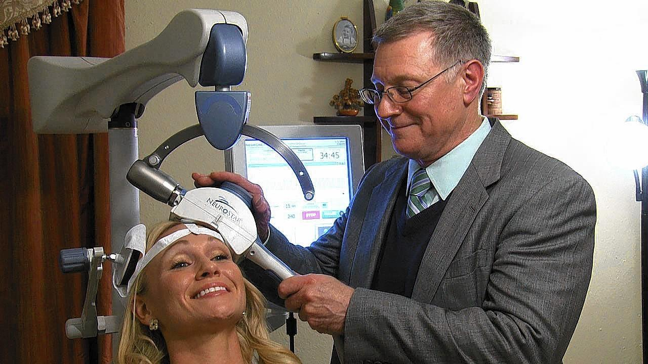 Kelsey Popa, a patient, with Dr. Scott Farmer, who is using Transcranial Magnetic Stimulation (TMS), which targets key areas of the brain with magnets.