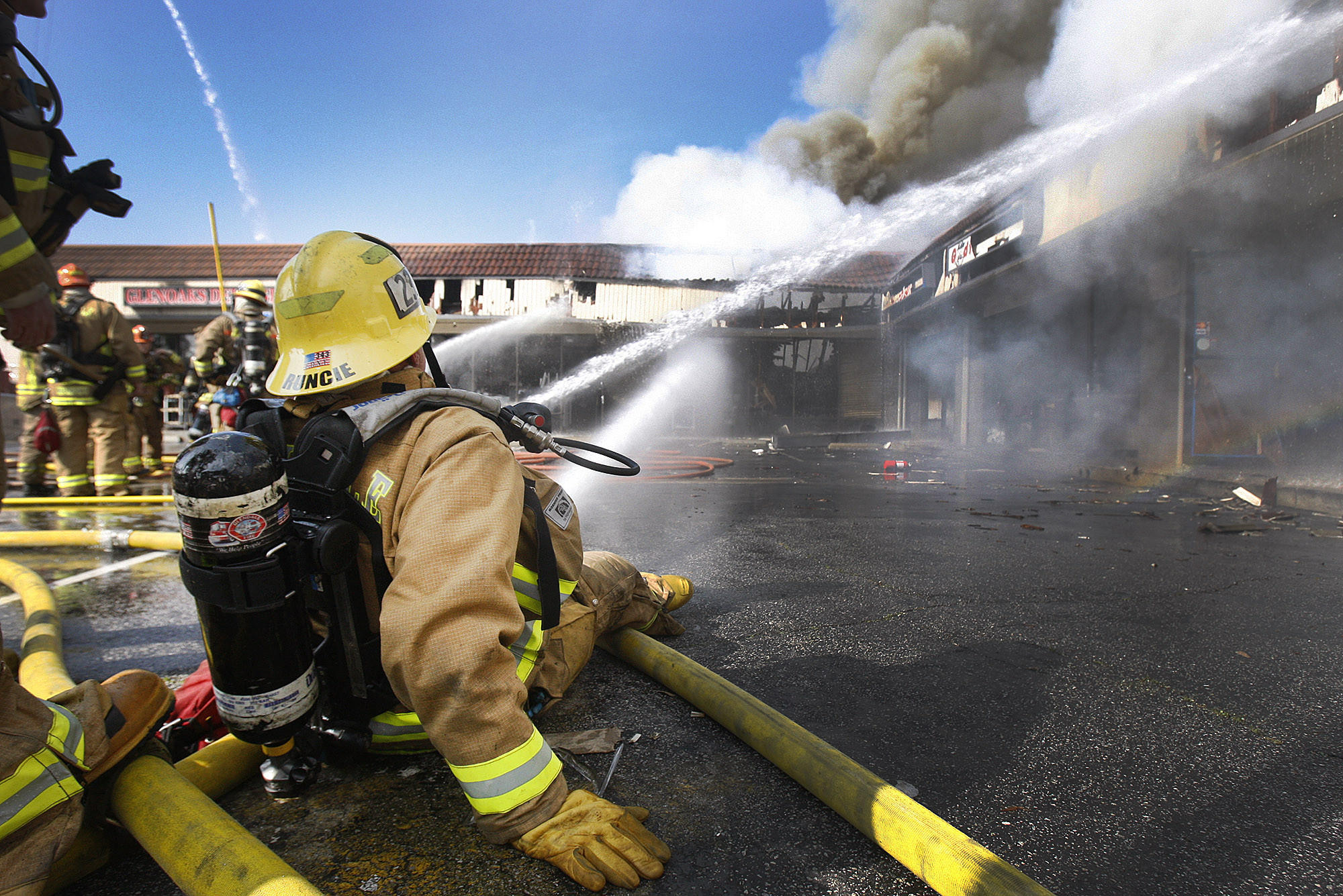 A fireman from Glendale station 23 holds a stream from a line of hose steady on a hot spot at the scene of an intense fire in a strip mall on the corner of Howard Street and Glendale Blvd. in Glendale on Monday, February 10, 2014.