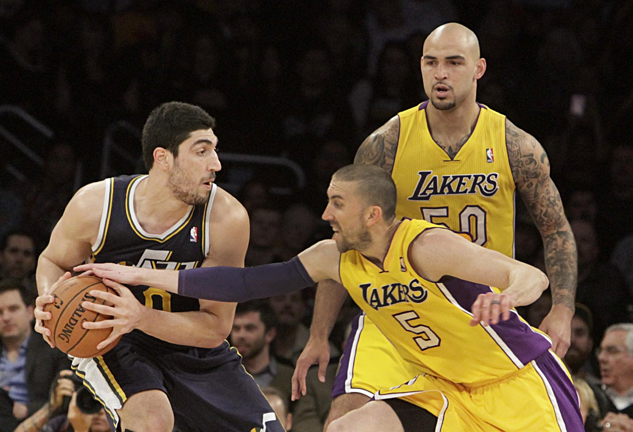 Utah's Enes Kanter holds the ball as Steve Blake reaches in during the second half of the Lakers' loss Tuesday to the Jazz, 96-79, at Staples Center.