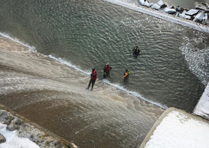 Rescuers work at the base of Atkisson Dam in Abingdon Wednesday morning, where a man, in red, suspended himself from a rope on the dam's spillway. The man was taken to a local hospital and received a citation for trespass. The dam is owned by the U.S. Army.