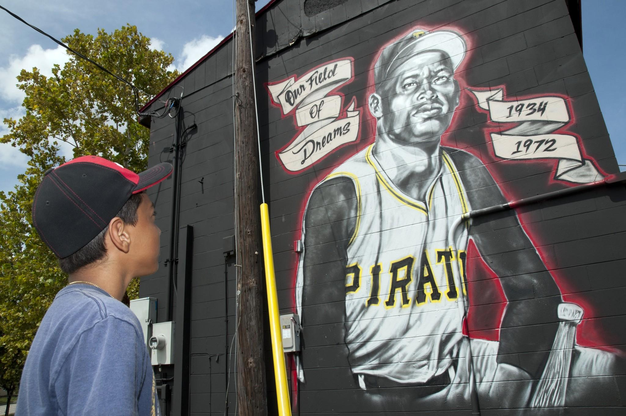 A child looks at a mural of Roberto Clemente by artist Hector Nazario.