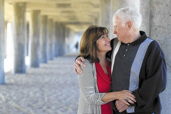 Ed Moynagh, 83, and wife Mary, 64, pose for a portrait underneath the Huntington Beach Pier on Wednesday. The couple met each other at the pier in August 2012 and later got married on Feb. 13, 2013.