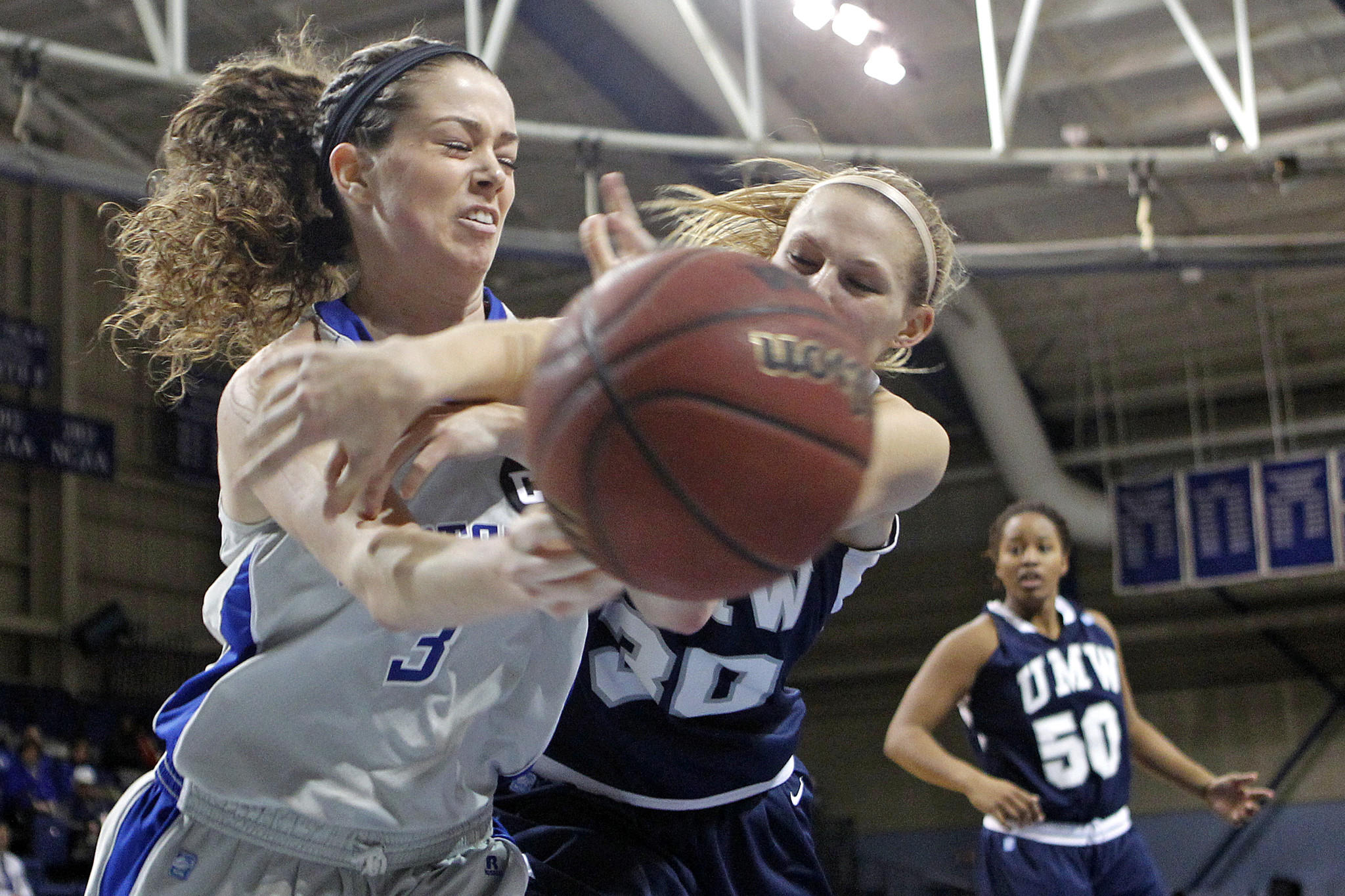 Christopher Newport University's Kendra Stone, left, battles for a loose ball with University of Mary Washington's Brieneke Matthes, center, during Wednesday's game at the Freeman Center.