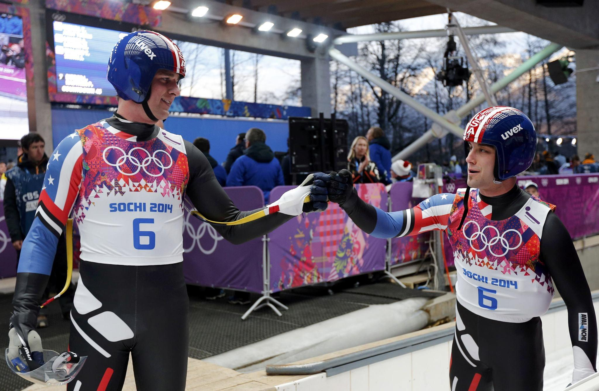 Pilot Christian Niccum (left) and Jayson Terdiman bump fists after competing in the men's luge doubles event.