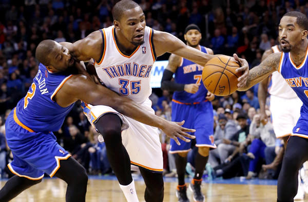 Thunder forward Kevin Durant (35) is fouled by Knicks guard Raymond Felton (2) as he drives between Felton and guard J.R. Smith in the fourth quarter of a game on Sunday in Oklahoma City.