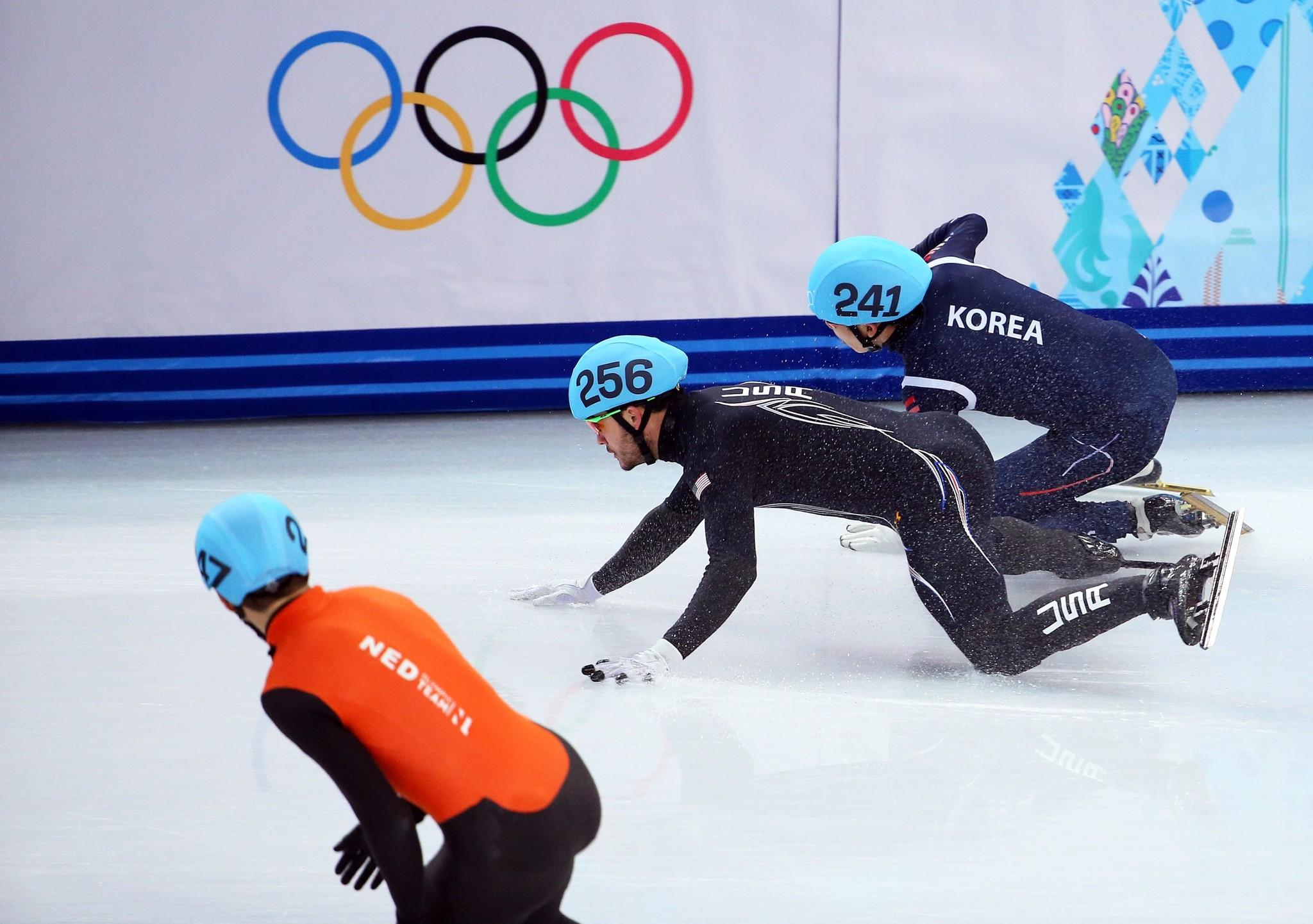 Eduardo Alvarez of the United States and Ho-Suk Lee of South Korea collide and fall as they compete in the Short Track Speed Skating Men's 5000m Relay Semifinal.