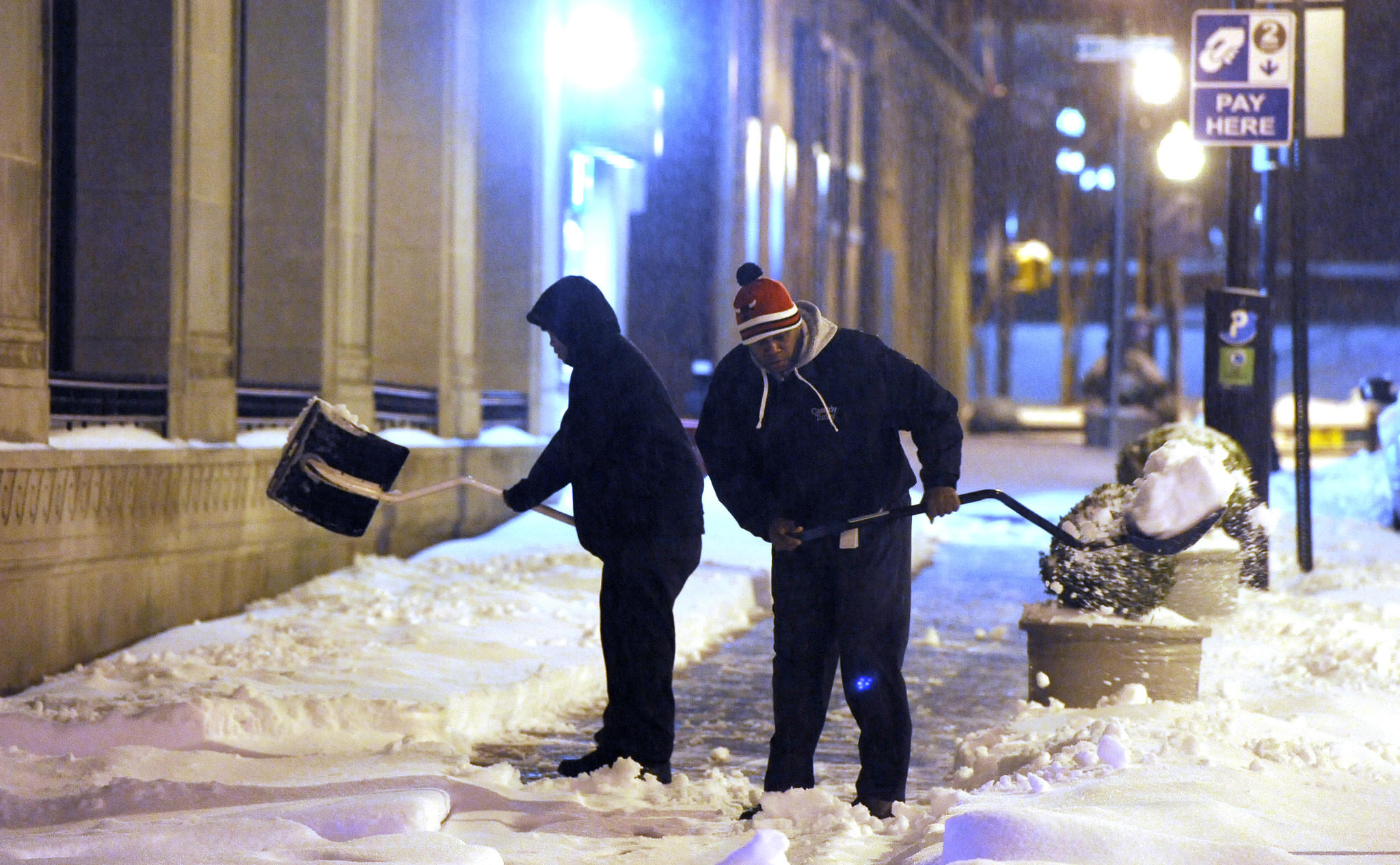Two men work together to shovel snow on Redwood Street early one morning during a snowstorm downtown.