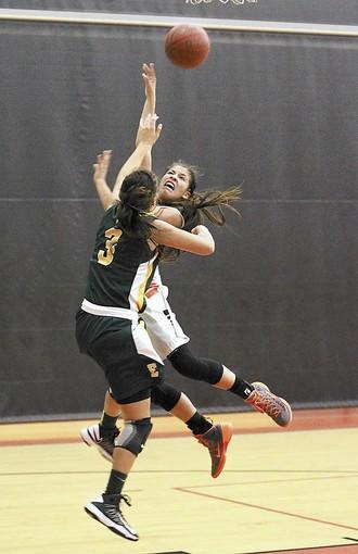 Huntington Beach High's Paola Roa drives to the basket after a breakaway and is fouled by Edison's Loli Gomez.