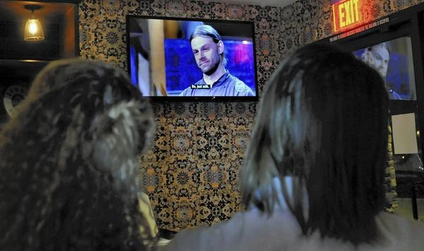 "Chef Elisha Irland on the big screen TV. Chefs of the Flintridge Proper Restaurant and Bar, Elisha Irland and Afton Bernard Farnsworth, were on hand to view a live showing of ""Chopped,"" a reality TV food show. Irland and Farnsworth were both contestant chefs on the Food Networks show."