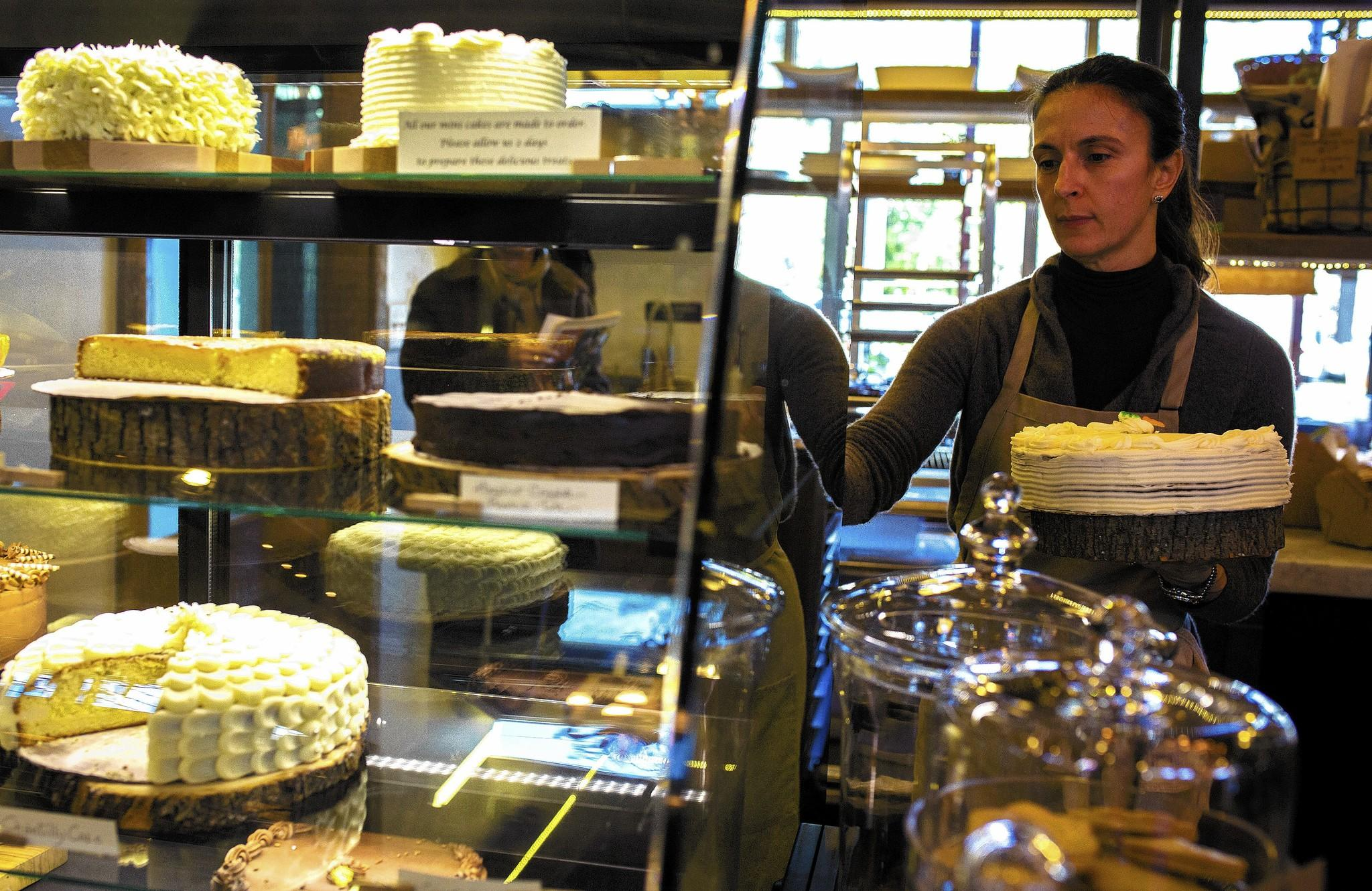 Elisa Scarpa, owner of Fatto in Casa, fills the dessert case in her store at East End Market.