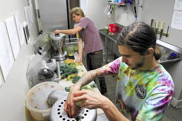 Owner Chase Bray, 27, top, and employee Jake Massanari, 21, blend fresh vegetables and fruits as they fill an order at PorroVita, a smoothie and juice bar in Newport Beach.