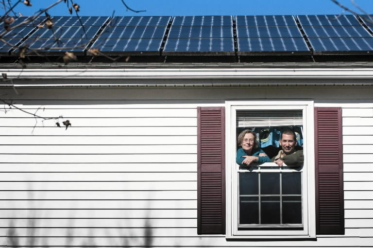 Melissa Everett and Greg Mark of the Enfield Clean Energy Committee look out from a second story window in Mark's Enfield home, where he installed panels for a 7.8 KW solar system.