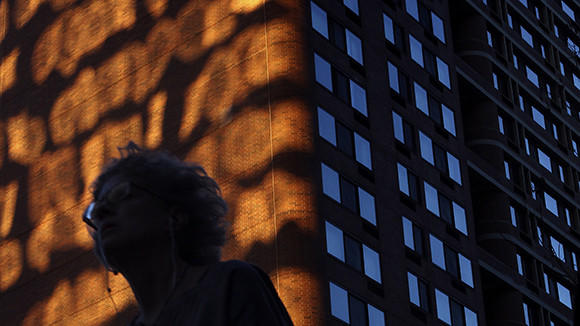 A woman walks on the corner of North Fairbanks Court and East Ohio Street as the sun reflects light onto The Grand Ohio Condominiums on Thursday, Sept. 26, 2013 in Chicago.