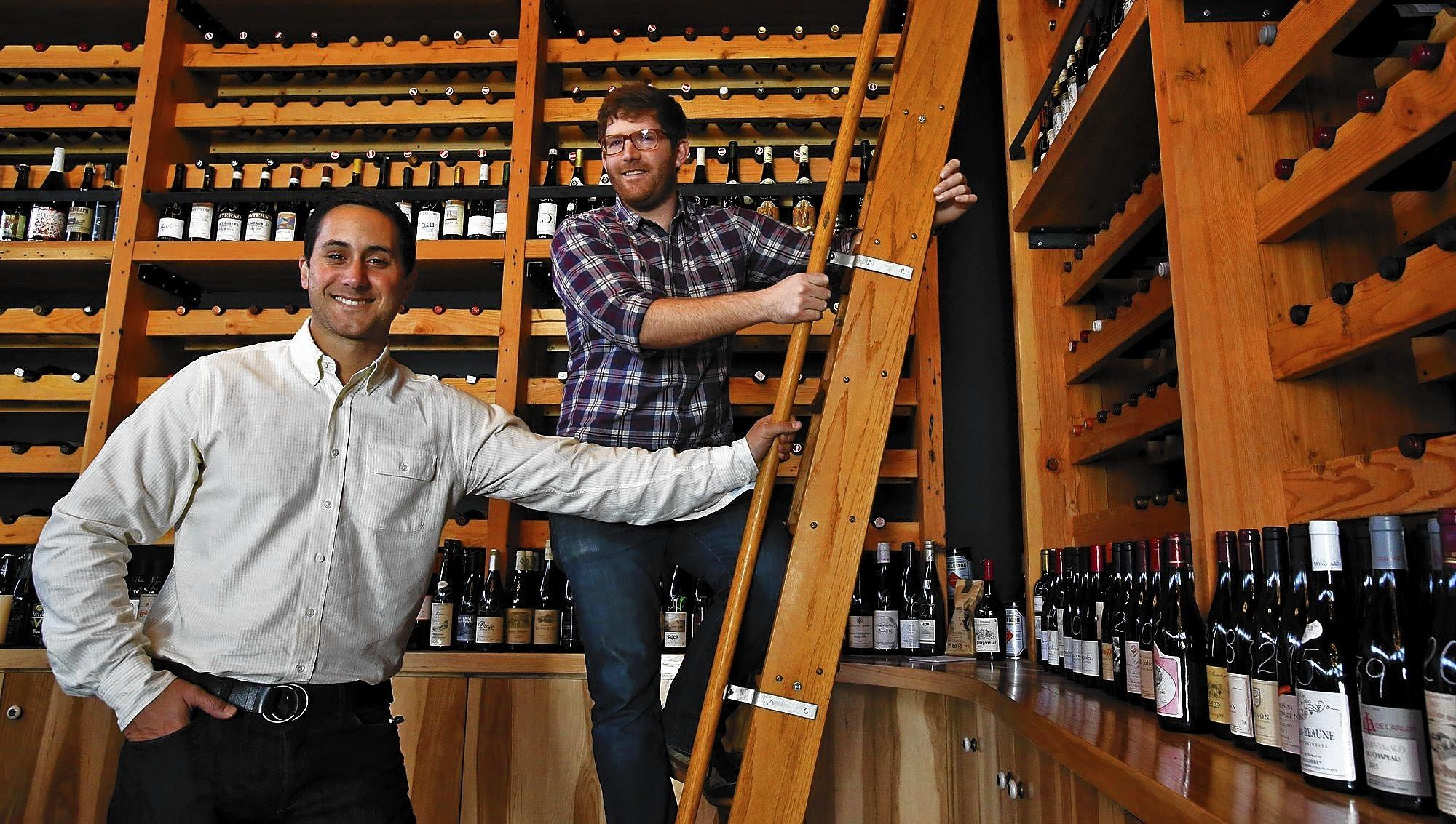 Brian McClintic, left, and Eric Railsbackpose at their wine shop Les Marchands in Santa Barbara.