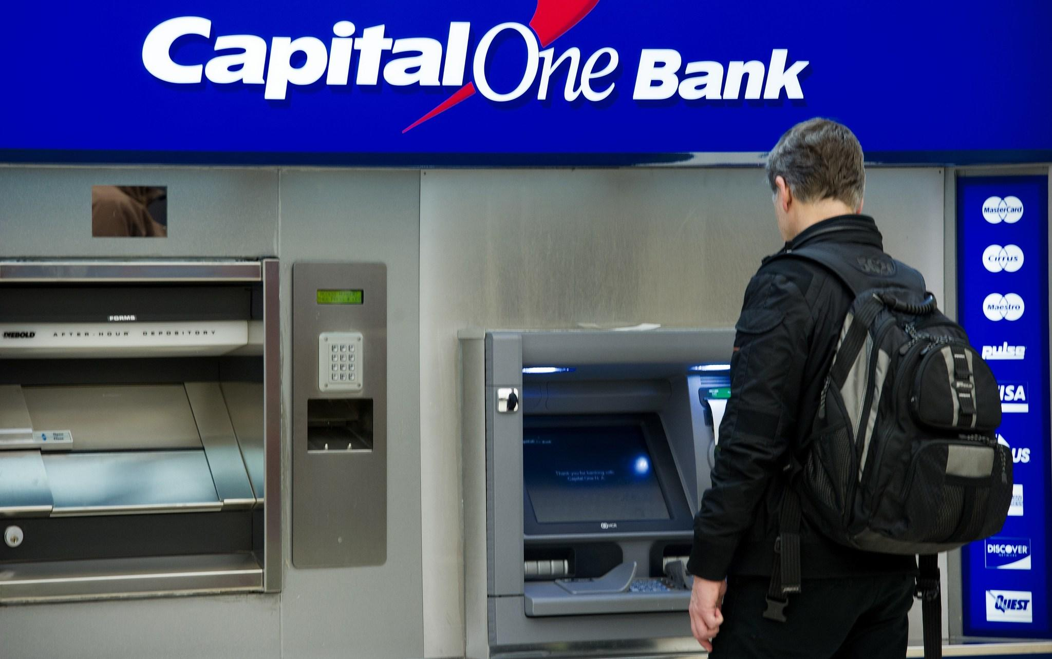 An airline traveler uses a Captial One ATM machine after landing at Dulles International Airport (IAD).