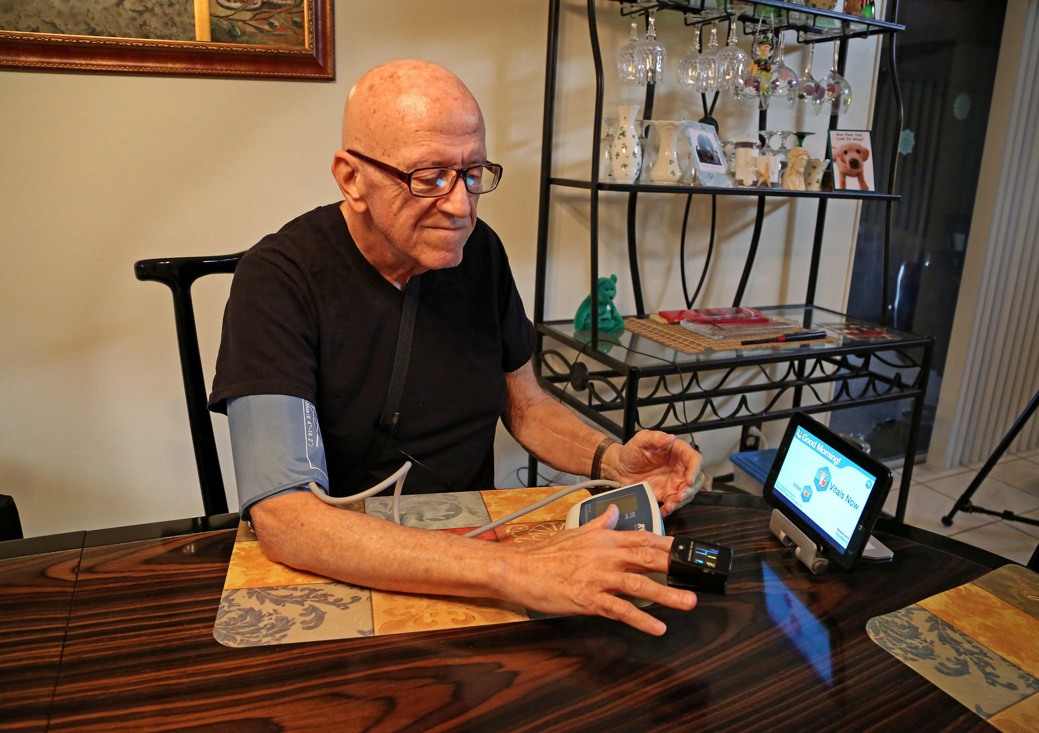 Ralph DeLuca, 72, a recovering heart attack patient, is monitored continuously through Memorial Regional's Home Health Services program. He uses a computer tablet at home hooked up to diagnostic equipment, which sends vital sign results directly to his doctor. (Susan Stocker/Sun Sentinel)