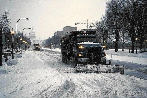 Snow plows travel along Pennsylvania Avenue to clear the roads after snow began falling overnight in Washington, early February 13, 2014. REUTERS/Jonathan Ernst