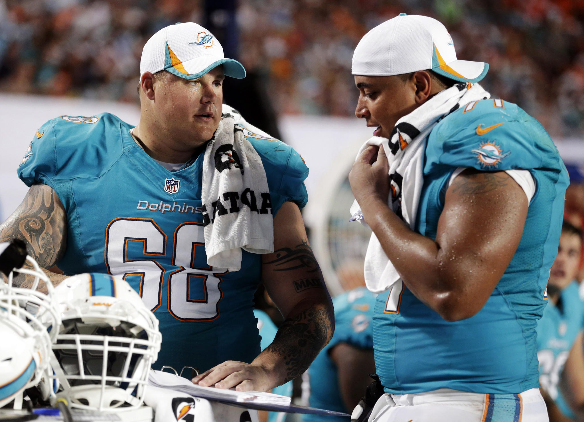 Miami Dolphins guard Richie Incognito (68) and tackle Jonathan Martin (71) look over plays during an NFL preseason football game against the Tampa Bay Buccaneers in Miami Gardens, Fla.