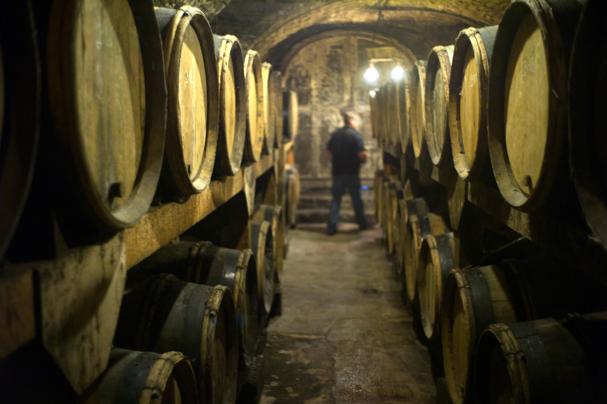 A person walks past barrels of wine stored in the cellar of the Chateau l'Etoile vineyard in l'Etoile.