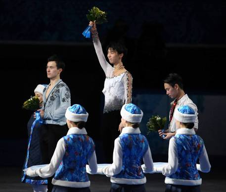 Yuzuru Hanyu, center, of Japan, celebrates after winning the gold medal in men's figure skating at the Iceberg Skating Palace during the Winter Olympics. Patrick Chan of Canada, left, won the silver medal and Denis Ten, right, won the bronze.