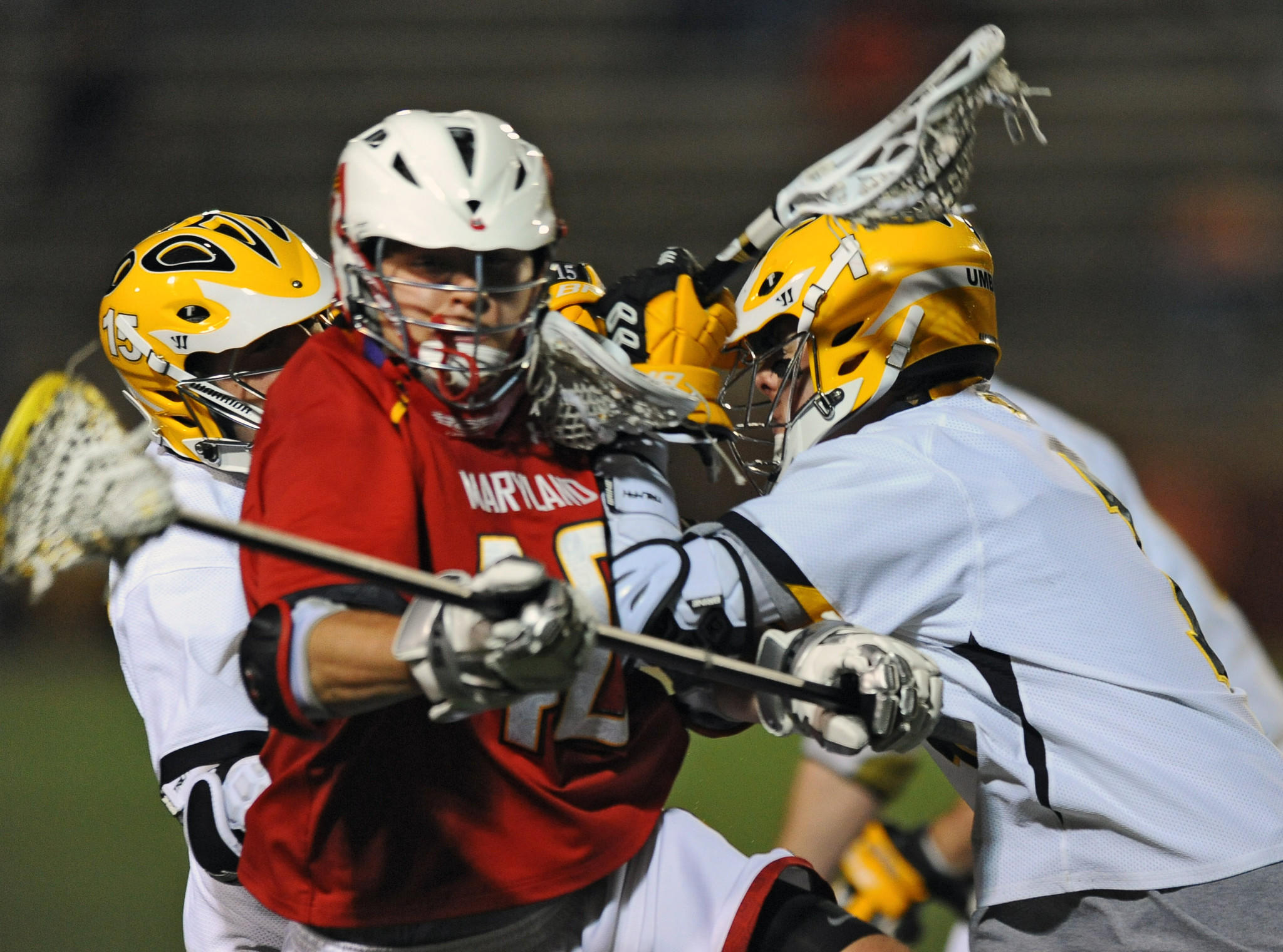 Maryland's Brian Cooper, center, is double-teamed by UMBC's Conor Finch, left, and Joe Lustgarten, right, in the second quarter of an eventual 8-7 Retrievers win in 2012.