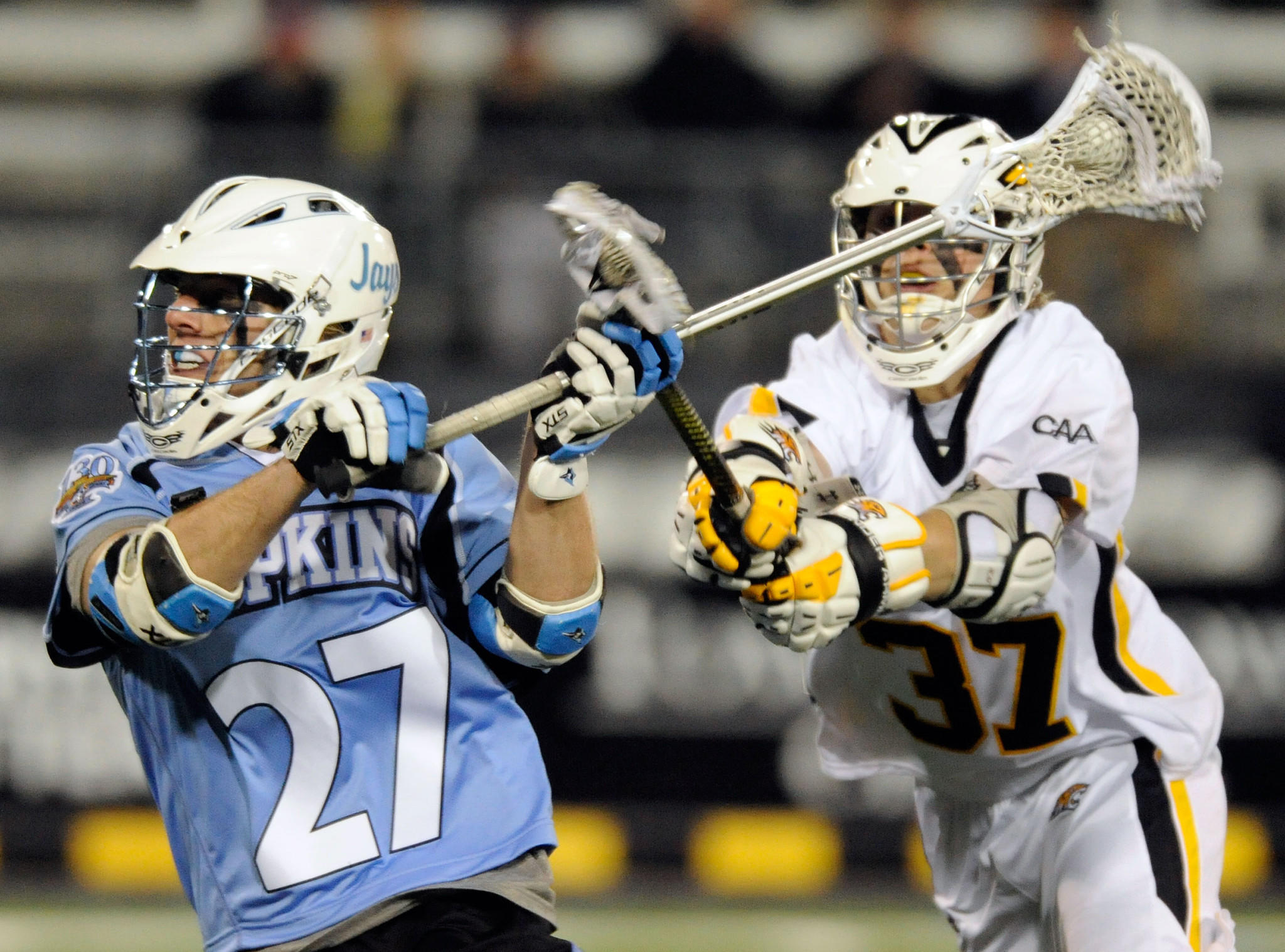 Towson's Dan Livingston, right, checks Johns Hopkins' Rob Guida in the first half of an eventual 12-6 Blue Jays win last season. The Tigers have lost 18 straight against their intrastate rival.