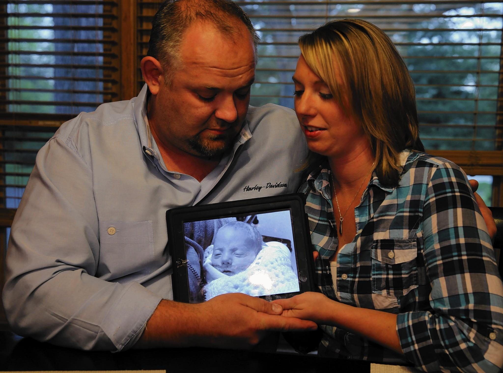 Elizabeth and Phil Peszat hold a photo of their son, Phil, who died last year when he was 7 weeks old. Elizabeth Peszat donated the breast milk that she continued to pump after his death.