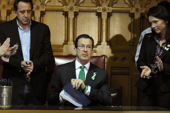 Between Sandy Hook parents Neil Heslin, left, and Nicole Hockley, Gov. Dannel Malloy finishes signing into law one of the country's gun control bills in April 2013.