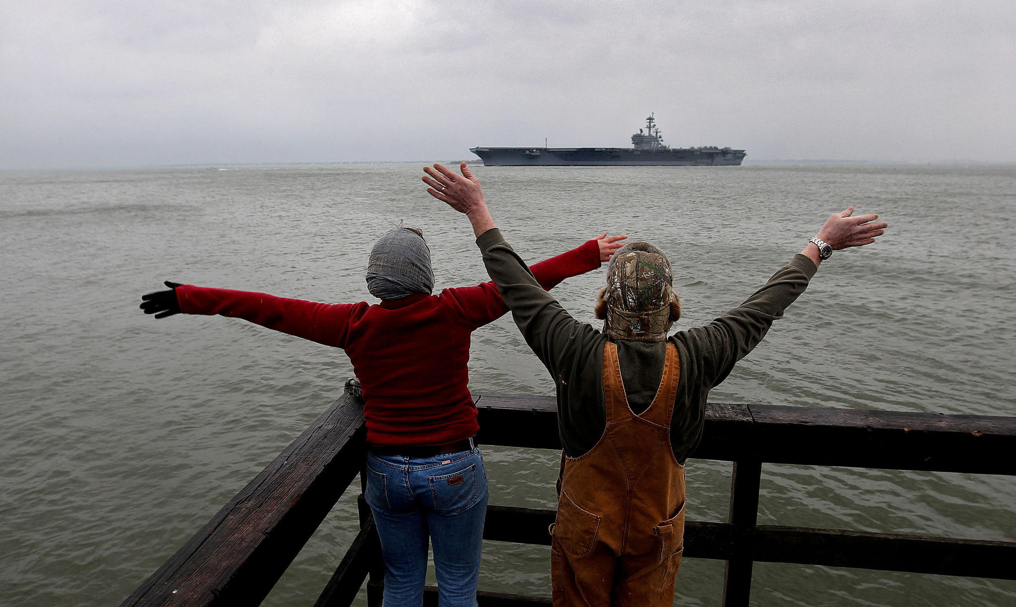 Sam Treas and her father Mike Berry wave to the USS George H.W. Bush and Sam's husband PO2 Corey Trese from Engineer Wharf Saturday. The ship will be gone for nine months.