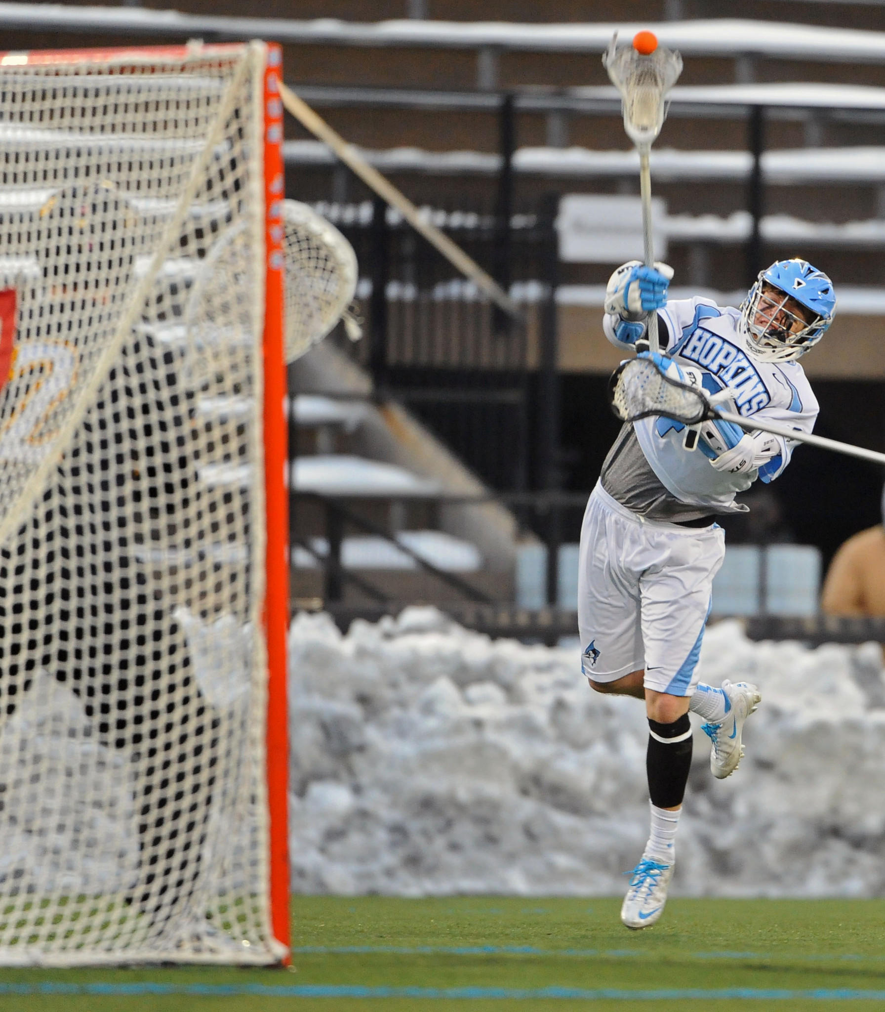 Johns Hopkins' Ryan Brown, right, shoots and scores against Towson in the third quarter of a 15-8 Blue Jays win last Saturday.