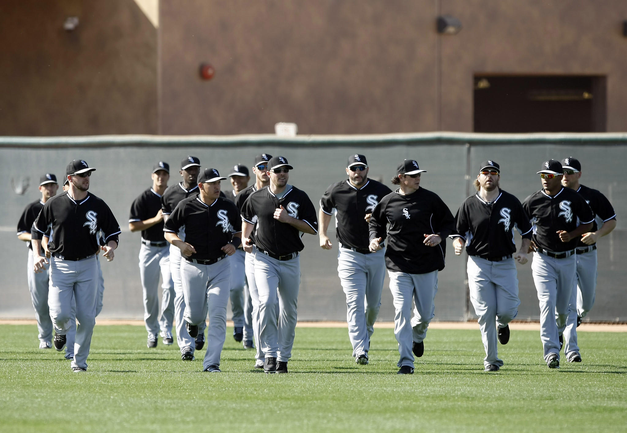 Chicago White Sox players run on the field during spring training at Camelback Ranch.