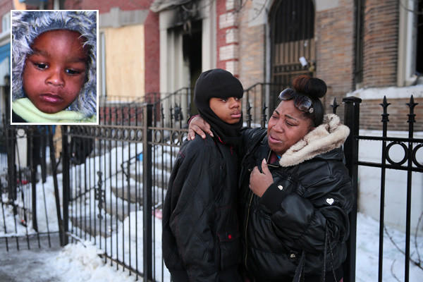 Donte Benamon, 14, hugs family friend Tamara Slater outside of his burned out home after an extra-alarm fire killed his 3-year-old brother, Jaantwiaon Edwards (inset photo) and critically injured another child when it swept though two homes Friday night in the South Austin neighborhood.