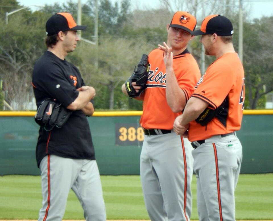 From left to right, Orioles pitchers Miguel Gonzalez, Zach Britton and Evan Meek talk during spring training Saturday in Sarasota, Fla.